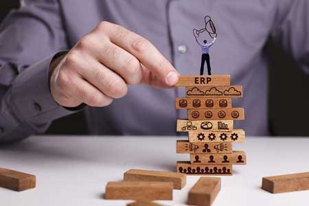 man stacking blocks to show competitive advantage of erp